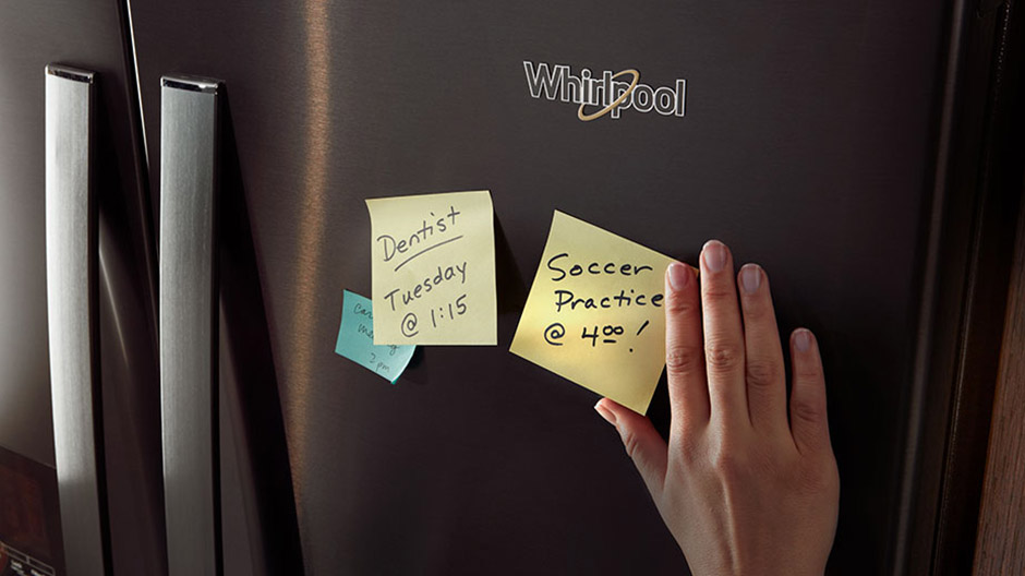 Front of the Fingerprint-Resistant Black Stainless Steel refrigerator with reminder notes stuck to it.