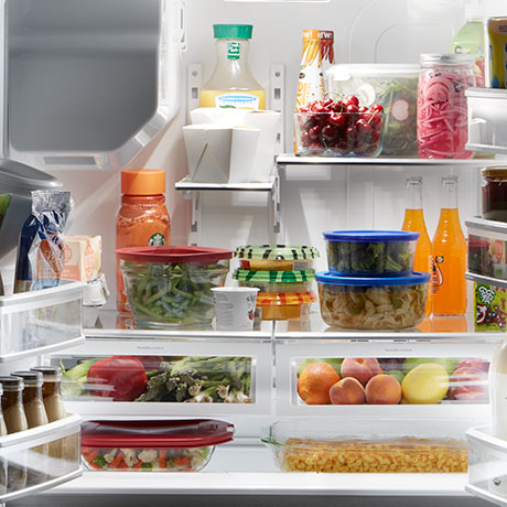 Interior of loaded refrigerator with all items fully lit.