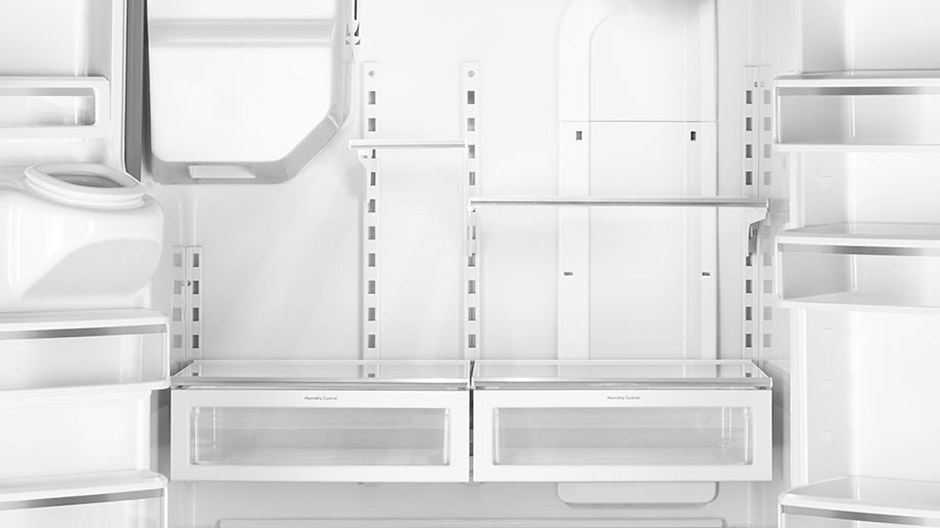 Empty interior of the refrigerator showing many movable shelves and door bins.