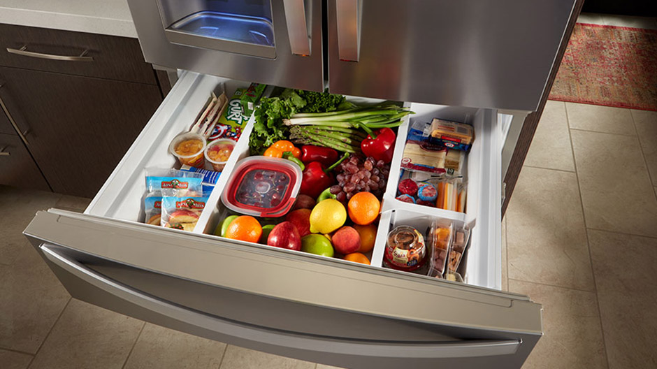 Fully extended refrigerator drawer filled with fruits, vegetables and snacks.